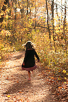 A young girl runs through the forest on an autumn sunset.