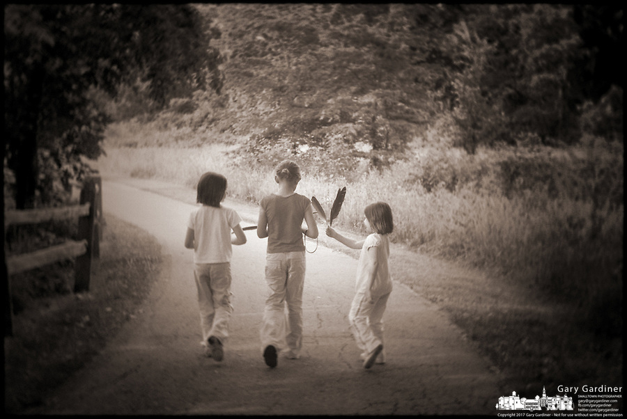 Brown toned, faded, old style photo of children walking along path at lake
