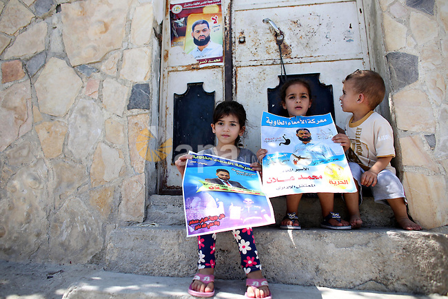 Relatives of Palestinian prisoner in Israeli jails Mohammad Allan, hold his portraits at the entrance of his house in the village of Ainabos, south of Nablus in the occupied West Bank, on August 9, 2015. The Israeli military prosecutor intends to request court permission on Saturday to force-feed hunger striking prisoner Mohammad Allan, the Palestinian minister of prisoner affairs, Issa Qaraqe announced on Friday. Allan, a lawyer from the occupied West Bank city of Nablus, has been on hunger strike for at least 50 days in protest of his detention without charge or trial since his arrest in November. Photo by Ahmad Talat