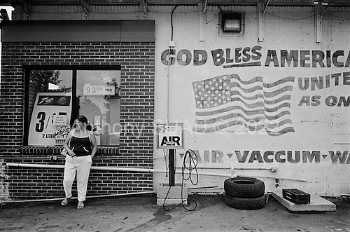 Buffalo, New York<br /> USA<br /> July 12, 2010<br /> <br /> A woman who has just been forced from her home charges her cell-phone battery at an electrical outlet located outside of a gas station.