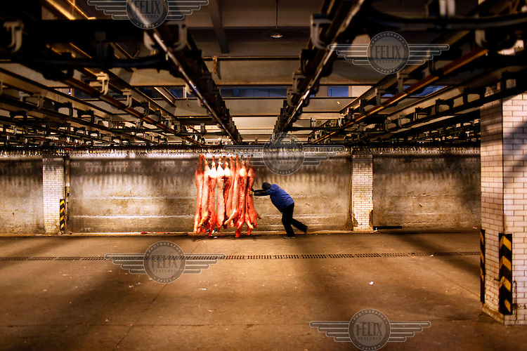A worker moves a rack of pig carcasses at a meat wholesale and distribution centre.