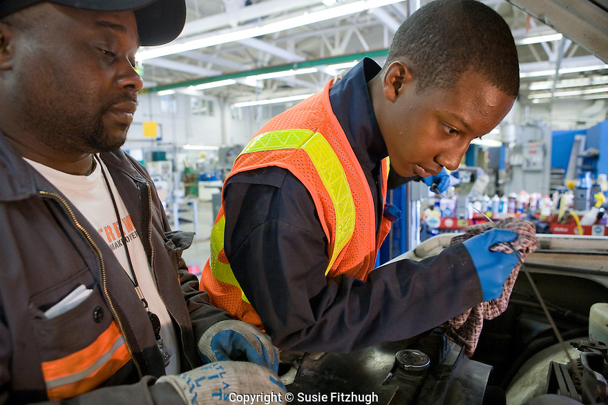 As part of an internship program at Rainier Beach High School, Marcusallen Wells, a Junior at RBHS, works with Port of Seattle Auto Repair Tech Ben McDaniel.