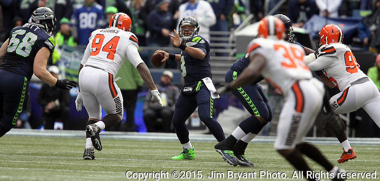 Seattle Seahawks quarterback Russell Wilson looks to pass against the  Cleveland Browns at CenturyLink Field in Seattle, Washington on December 20, 2015. The Seahawks clinched their fourth straight playoff berth in four seasons by beating the Browns 30-13.  ©2015. Jim Bryant Photo. All Rights Reserved.