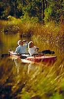 Couple birdwatching from kayak. river, leisure, hobbies, retirement, outdoors, boats, couples, birding. Gulf Shores Alabama United States.