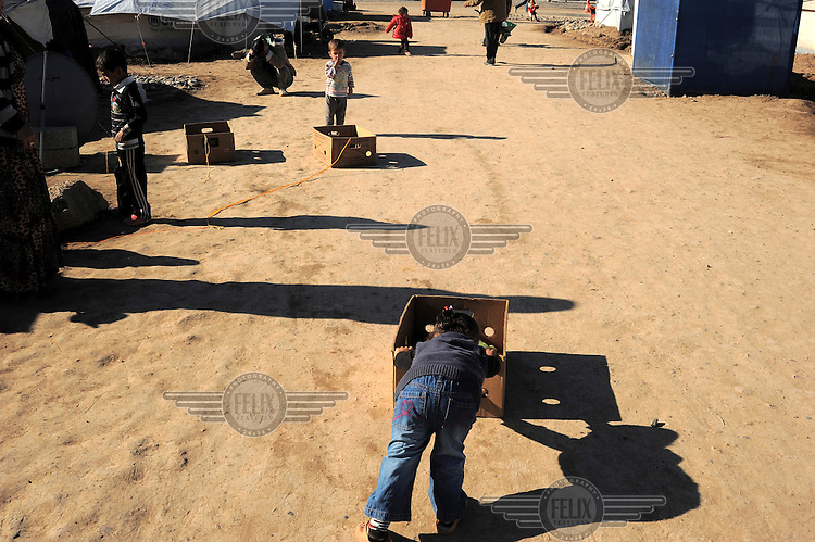 Children playing with boxes at the Kawergosk Syrian Refugee Camp.