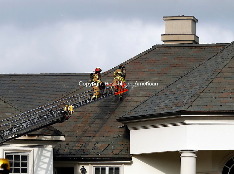 Middlebury, CT- 03 July 2014-070314CM06-  Firefighters standby to cut a hole in the roof at 725 Breakneck Hill Rd in Middlebury on Thursday.  Firefighters from Middlebury, Southbury, Watertown and Waterbury responded to fight the structure fire at the home.   Christopher Massa Republican-American