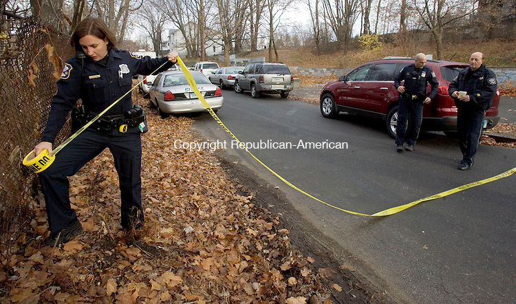WATERBURY, CT. 28 November 2011-112811SV04--At left, Officer Dawn Spellman tapes off a crime scene as police investigate a murder at 71 River Street in Waterbury Monday.<br /> Steven Valenti Republican-American