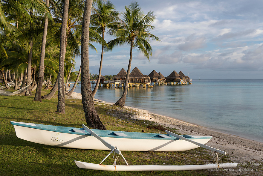 Rangiroa Atoll, Tuamotu Archipelago, French Polynesia; view of the overwater bungalows and an outrigger sailboat at the Hotel Kia Ora Resort and Spa in late afternoon sunlight