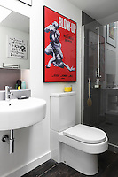 A 1960s film poster adds a bold dash of colour to the simple white and grey bathroom