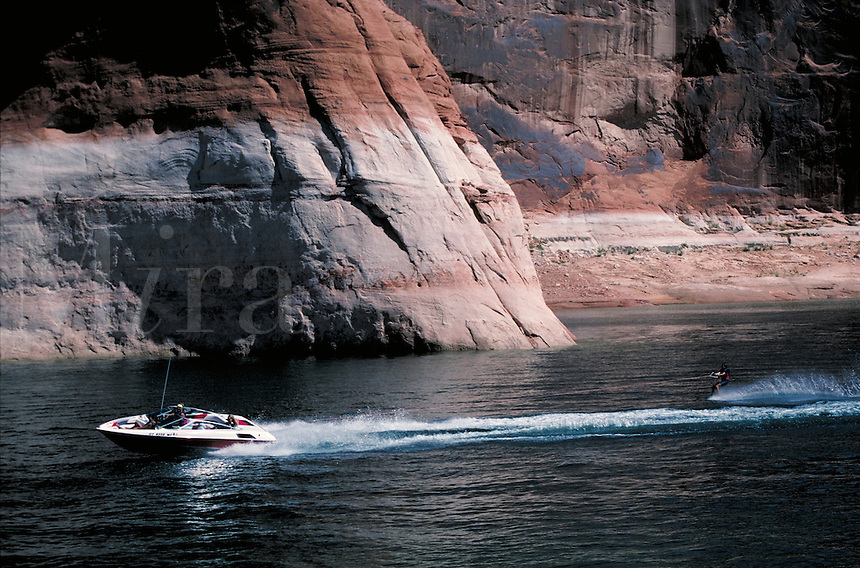 A waterski boat pulls skier in calm side canyon at Lake Powell. sports, boats,. Utah, Lake Powell.