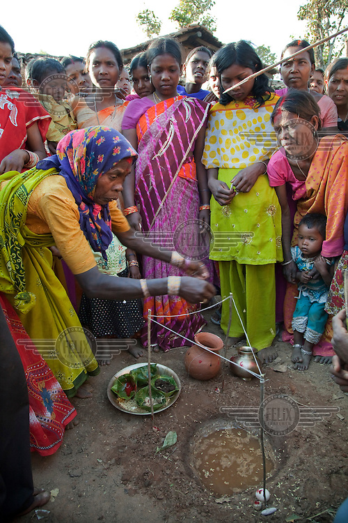 An elderly woman performs a purification ceremony with members of the bride's family to exorcise the bride's past-life prior to her wedding ceremony. An arrow protrudes from the upper right symbolizing the shooting away of the bride's past: One of the wedding traditions of the Santhal Adivasi tribal people...