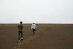 Snowy Plover (Charadrius nivosus) biologists, Karine Tokatlian and Ben Pearl, walking through restored salt pond, Eden Landing Ecological Reserve, Union City, Bay Area, California