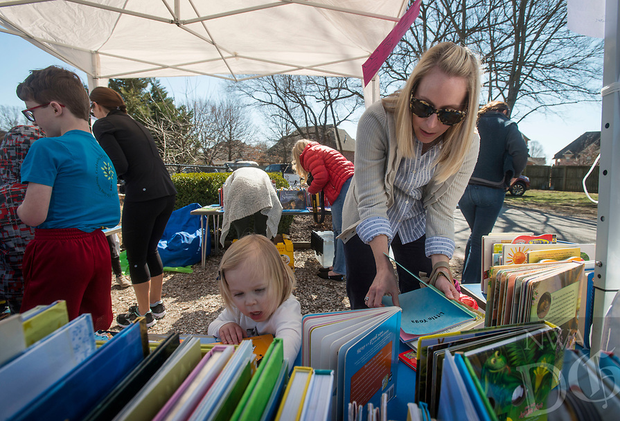 NWA Democrat-Gazette/BEN GOFF @NWABENGOFF<br /> Christine Howard and daughter Hannah Howard, 2, a student in the school's toddler program, of Rogers browse the book sale Friday, March 2, 2018, during a celebration of National Montessori Education Week at Walnut Farm Montessori School in Bentonville. Gov. Asa Hutchinson signed a proclamation recognizing the week in Arkansas and the educational philosophy founded more than 100 years ago by Dr. Maria Montessori. Students at the school celebrated with songs and a book and craft sale to raise money for Little Rock-based nonprofit Heifer International, in keeping with Dr. Montessori's phillosophy of global citizenship.