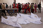 Red Crescent workers stand near the bodies of dead fighters loyal to Free Syrian Army during an exchange of dead bodies between Free Syrian Army and Syrian Government forces, in Bustan al-Qasr district in the east of the northern Syrian city of Aleppo on June 11, 2015. Photo by Ameer al-Halbi