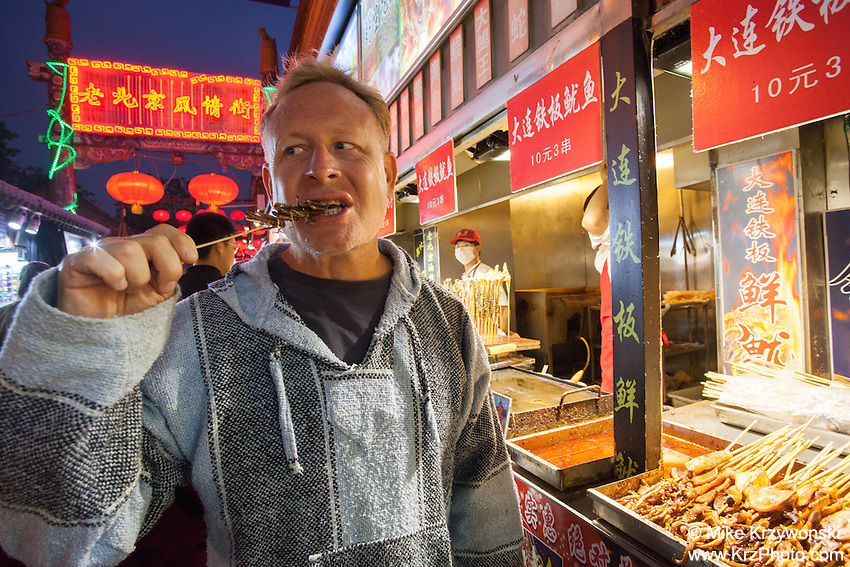 Caucasian male tourist eating cooked locusts on a skewer at the night market in Beijing, China