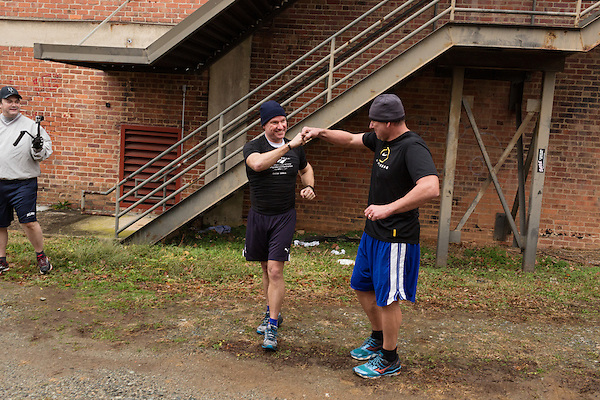December 22, 2014. Lexington, North Carolina.<br />  Mayor Newell Clark fist bumps his cousin Stan Lanier after doing a long arm climb and pull-ups on a factory staircase.<br />   Newell Clark, the 43 year old mayor of Lexington, NC, leads a group of friends and colleagues on a 4 times a week exercise routine around downtown. The group uses existing infrastructure, such as an abandoned furniture factory, loading docks, stairs, and handrails to get fit and increase awareness of healthy lifestyles in a town more known for BBQ.<br /> Jeremy M. Lange for the Wall Street Journal<br /> Workout_Clark
