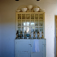 The rustic kitchen dresser houses a collection of oil lamps which are used daily since the house has no electricity