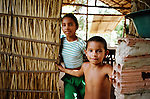Two children pictured at their home, a traditional reed hut in a small settlement in a protected reserve in the rainforest. The Floresta Nacional do Tapajos (FLONA), a 6500 km2 protected reserve, was home to several small communities which lived on the banks of the Rio Tapajos river. The communities did not have electricity or running water and access to the villages was by unpaved dirt roads from Santarem and Highway BR163.