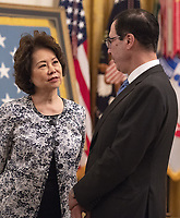 United States Secretary of Transportation Elaine Chao, left, in conversation with US Secretary of the Treasury Steven Mnuchin, right, prior to the arrival of US President Donald J. Trump who will make remarks at the Congressional Medal of Honor Society Reception in the East Room of the White House in Washington, DC on Wednesday, September 12, 2018.<br /> CAP/MPI/RS<br /> &copy;RS/MPI/Capital Pictures