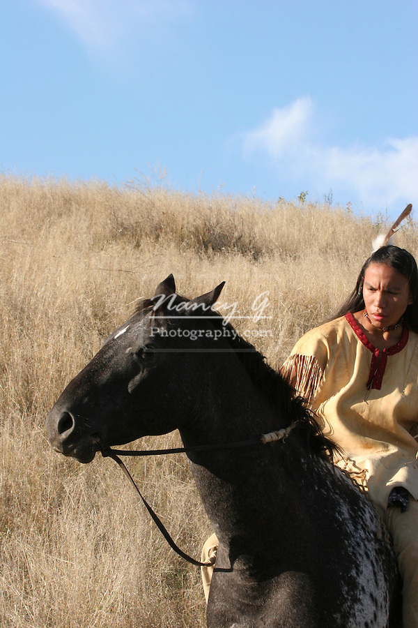 A Native American Indian boy on horseback riding an Appaloosa horse in the prairie of South Dakota