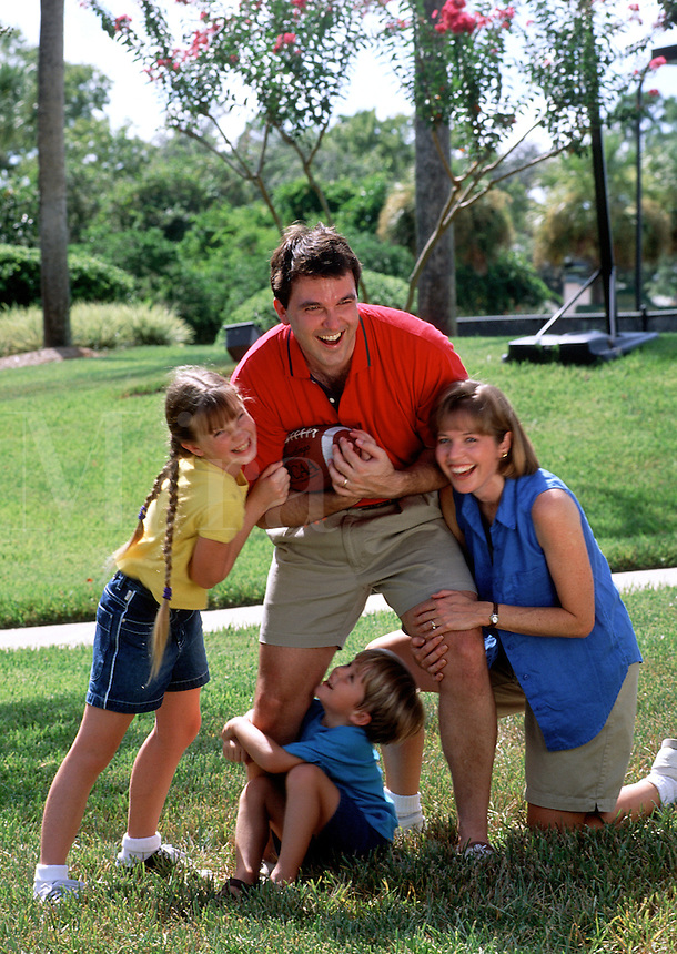 A young family portrait; mother father, son and daughter laughing and playing football on the lawn.