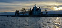 Sunrise silhouettes Sisters Island Lighthouse on a cool November morning in the St. Lawerence River shipping Channel in the 1000 Islands of upstate New York.