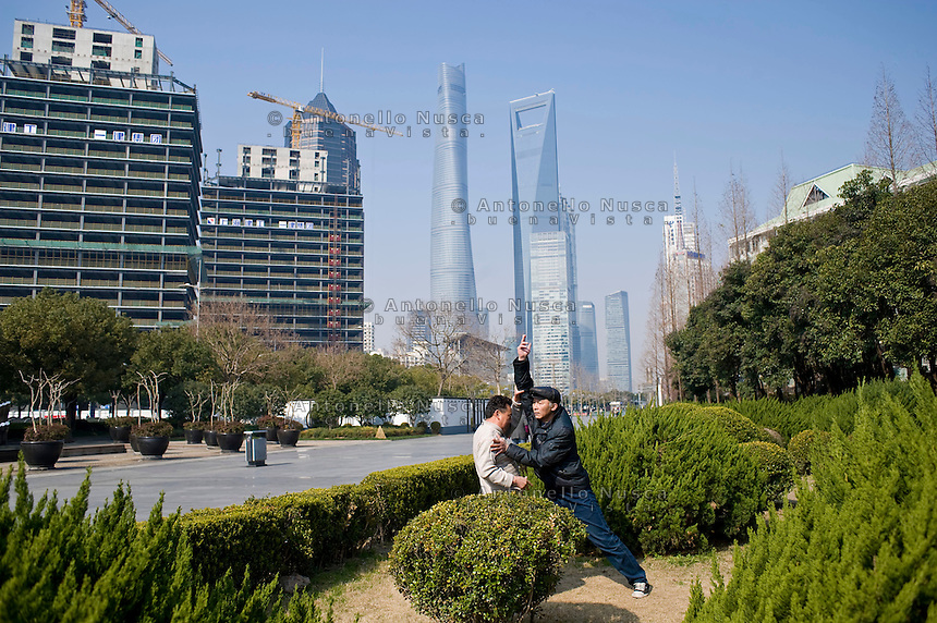 Due uomini praticano il tai chi chuan in una strada di Shanghai.<br /> People practicing tai chi chuan on the street
