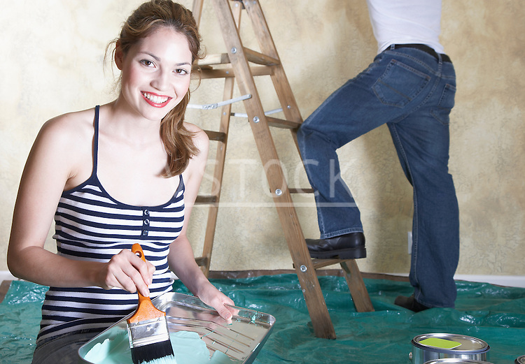 Portrait of young woman holding paint tray, man in background