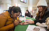 NWA Democrat-Gazette/BEN GOFF @NWABENGOFF <br /> Sowmi Nyam (left), a student from Bentonville and president of the Northwest Arkansas Community College International Club, paints a henna design on the hand of Belen Paneda, a student from Tontitown, Thursday, Nov. 15, 2018, at Northwest Arkansas Community College in Bentonville. The community college is celebrating International Education Week with events including movie screenings, food, yoga classes and a silent auction which ends Friday. Proceeds from the auction support scholarships for international students and other programs.
