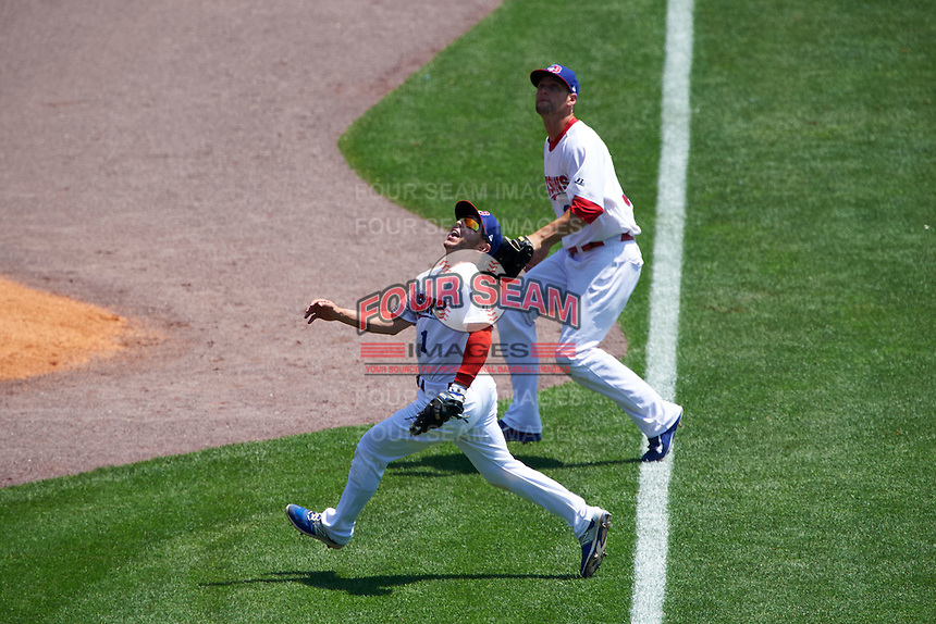 Buffalo Bisons shortstop Jonathan Diaz (1) tracks a foul ball pop up as outfielder Alex Hassan (39) backs up the play during a game against the Columbus Clippers on July 19, 2015 at Coca-Cola Field in Buffalo, New York.  Buffalo defeated Columbus 4-3 in twelve innings.  (Mike Janes/Four Seam Images)