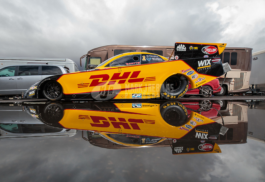 Feb 22, 2019; Chandler, AZ, USA; The car of NHRA funny car driver J.R. Todd reflects in a rain puddle as the car is towed to the staging lanes during qualifying for the Arizona Nationals at Wild Horse Pass Motorsports Park. Mandatory Credit: Mark J. Rebilas-USA TODAY Sports