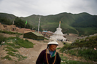 A Tibetan Buddhist pilgrim walks along a prayer path in Xiahe, Gansu, China. Xiahe, home of the Labrang Monastery, is an important site for Tibetan Buddhists.  The population of the town is divided between ethnic Tibetans, Muslims, and Han Chinese.