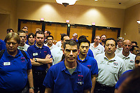 Jeffrey Kirk, 36, center, and other dealers wait to hear their table assignment at the 36th annual World Series of Poker at the Rio on Friday July 8, 2005 in Las Vegas, Nevada. Thursday marked the start of the no-limit Texas hold'em main event. Approximately 5,600 players are competing for a chance to win the first-place prize of roughly $7.5 million. (Photo by Landon Nordeman/ Getty Images)