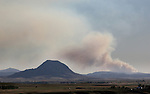 JUNE 25, 2016 -- A lightning strike Friday evening caused a fire on Crow Peak near Spearfish, S.D. that had grown to about 250 acres Saturday afternoon.  This image shows the fire in perspective with Bear Butte (left) taken approximately 20 miles east of Sturgis, S.D. at just after 7pm Mountain Time.  (Photo by Richard Carlson/dakotapress.org)