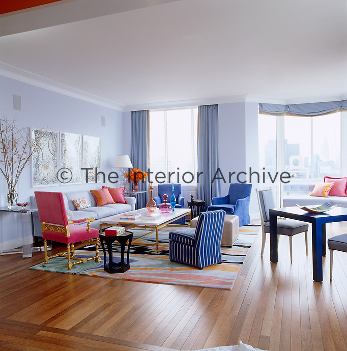 The spacious open-plan living area is furnished with antique and contemporary pieces and features a triptych by Ryan McGinness