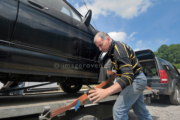 David Pile loading the Maestro / Land Rover Freelander Mule prototype CB40 brake test hack onto a trailer for transport to the Dunsfold Collection weekend. Dunsfold Collection of Land Rovers 2011, Dunsfold, Surrey, UK. --- No releases available, but releases may not be necessary for certain uses. Automotive trademarks are the property of the trademark holder, authorization may be needed for some uses. --- Vehicle Information: Vehicle belongs to the Dunsfold Collection of Land Rovers: Chassis number SAxxxx09, Registration G649 FKD, Engine 1.8 petrol , Gearbox 5-speed manual. --- Vehicle History: This strange looking van is a very important link in the Freelanders history. Based on a Maestro commercial van body shell this is one of around 25 built for on road testing of all Freelander running gear without taking full pre production prototypes in public view on the roads. Roll cage, disguised wheels, fuel fillers and registration plates would make this just another van if seen at night while testing. this mule as they were called was used for brake trials and would have covered many miles here and abroad towing a ballast trailer. Only 3 of the mules survive, all others being crushed. Two colours were seen around black and cream. Petrol and diesel, right and left hand drive were made building started in 1994 3 years before production.
