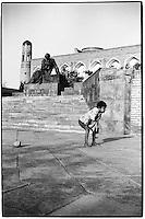 Uzbekistan - Khiva - Little boy playing football near Al-Khorezmi statue.