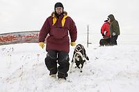 Veteran Iditarod musher Palmer Sagoonick, now a volunteer checker, walks a dropped dog to a waiting plane in Shaktoolik Monday during Iditarod 2008