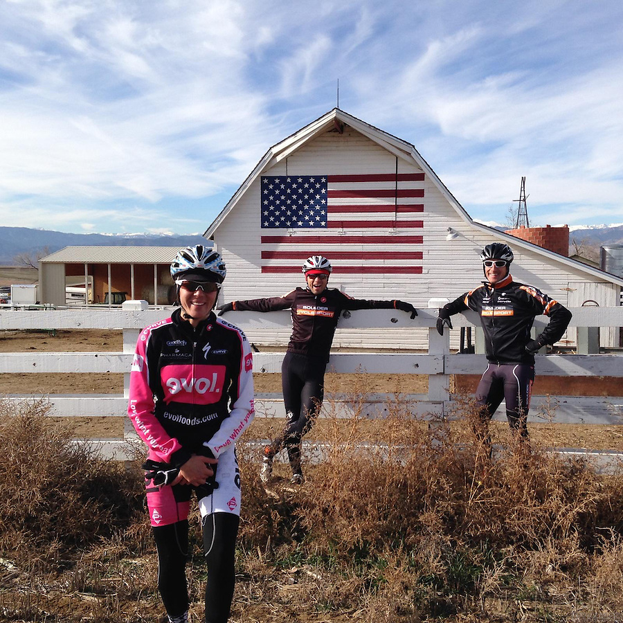 Cyclists pose in front of an American flag covered barn in north Boulder County, Colorado.