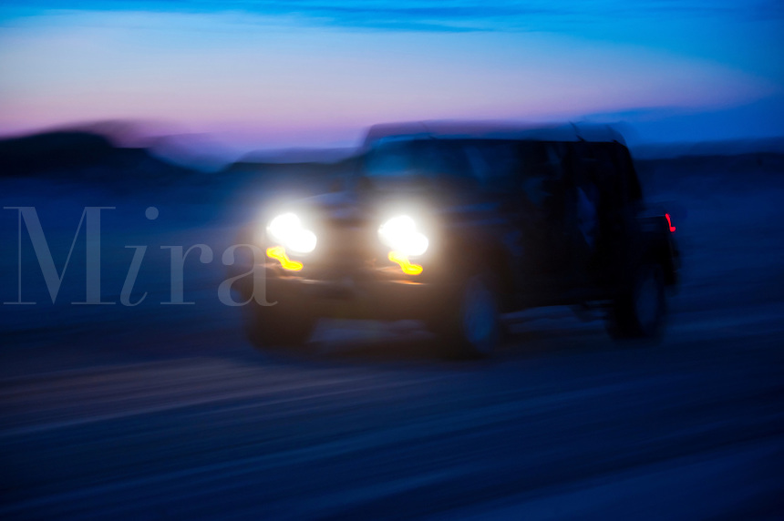 SUV riding off road at night.