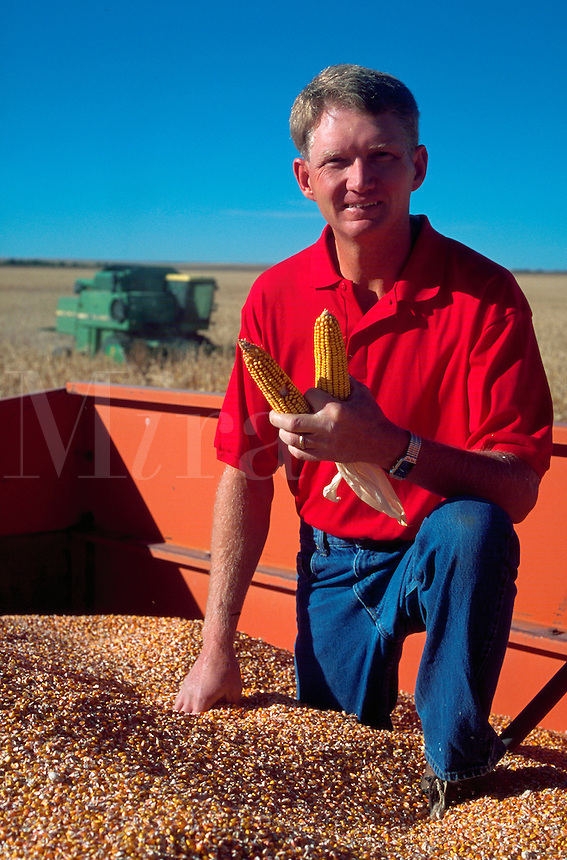 Portrait of a farmer with his corn harvest.