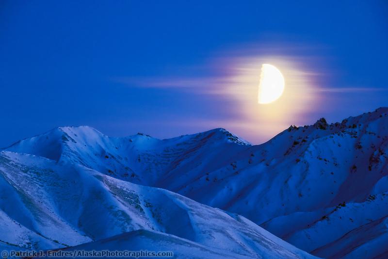 Quarter moon rises over the Alaska mountain range in Denali National Park, Alaska