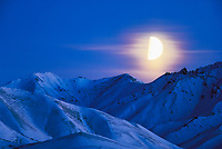 Quarter moon rises over the Alaska mountain range in Denali National Park, Alaska
