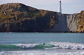 Surfer riding a wave below Castlepoint lighthouse.