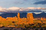 View of Balanced Rock, Turret Arch, and the La Sal Mountains, Arches National Park, Moab, Utah, USA with clouds at sunset.