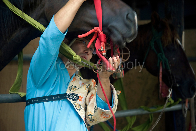 "A rider readies his mount prior to the ""yabusame-shinji"" horseback archery ritual on the final day of the Reitaisai grand festival at Tsurugaoka Hachimangu shrine in Kamakura, Japan on  14 Sept. 2012. The yabusame ritual is performed by members of the Ogasawara school, which began mounted archery rituals in the 12th century. .Yabusame was originated in middle of 6th century as a Shinto ritual. Today there are various styles and manners of Yabusame inherited by different shrines and particular families. It was common in the ancient past that the result of Yabusame depended on the number of targets successfully hit, and also fragments of the target were used to tell fortunes. The target and arrows used in successful shots were kept as amulets. The initiation of Yabusame in Tsurugaoka Hachimangu was 1186. Photographer: Robert Gilhooly"