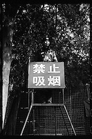 A Chinese security guard stands on a gantry as he monitors and prevents people from smoking at a Chinese New Year fair in Beijing, China, in February 2011. The Chinese sign reads 'smoking is prohibited'. (Leica M6, 35mm f2, Kodak Tri-X film)