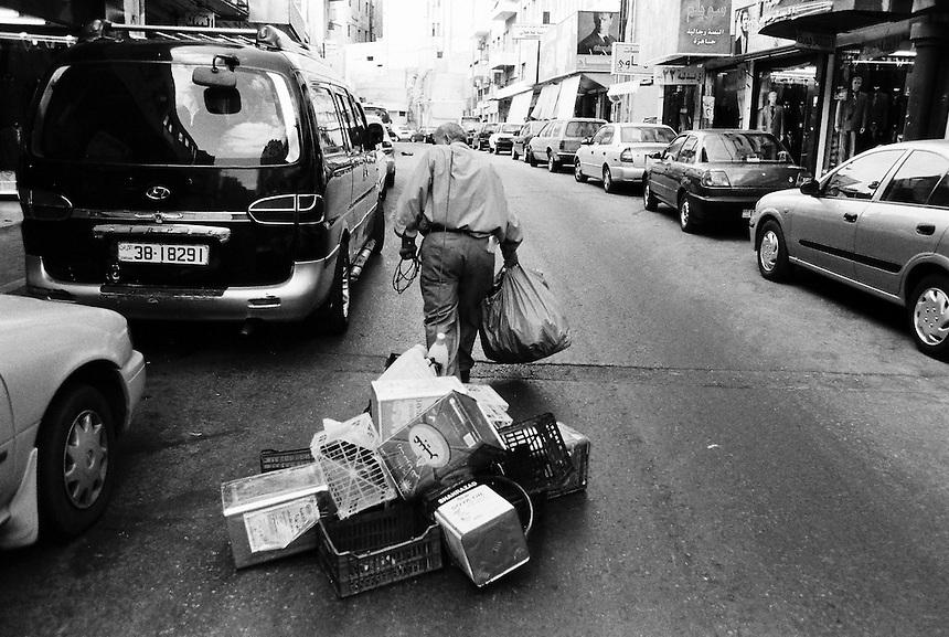 An Iraqi man drags trash through the streets of downtown Amman, Jordan, August 2009. Photo: Ed Giles.