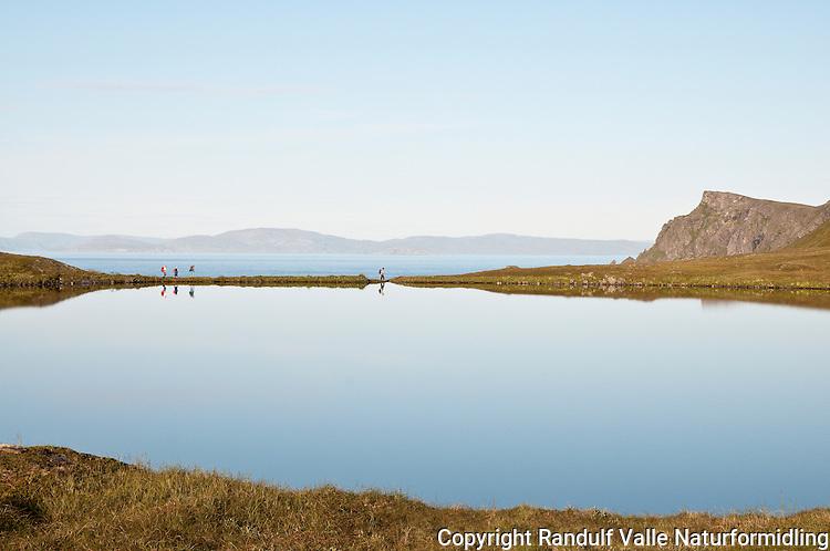Fotturister passerer Kjøttvikvannet på Sørøya en stille sommerkveld. ---- Hikers passing small lake on Sørøya.