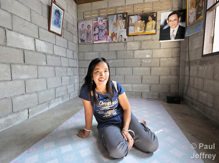 Sam Kaurwiriyatrakun is an HIV positive woman in the village of Toong-sa-tok in northern Thailand. Seen here in her home, with pictures of the country's royal family on the wall behind her, she is a member of a women's cooperative, supported by the monks of the local Hualin Buddhist temple, which sews clothing for sale in Japan and other foreign countries, yielding important income for the women and their families.
